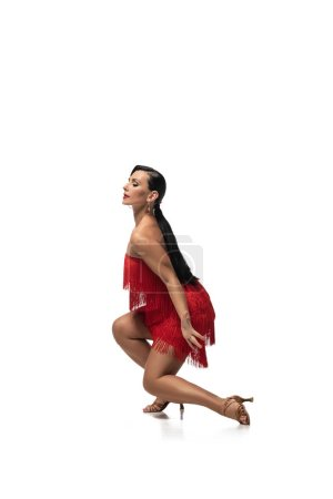 Photo for Elegant dancer squatting with closed eyes while performing tango on white background - Royalty Free Image