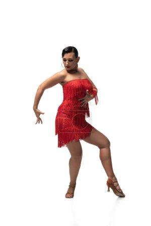 Photo pour Danseuse passionnée en robe élégante avec frange exécutant tango sur fond blanc - image libre de droit