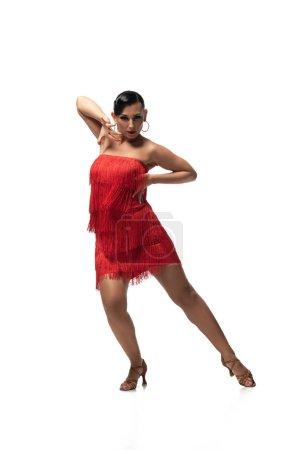 Photo pour Attrayant, danseur passionné en robe rouge avec frange regardant caméra tout en effectuant tango sur fond blanc - image libre de droit