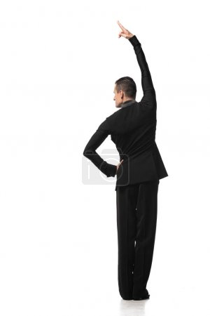 Foto de Back view of dancer in elegant black suit performing tango on white background - Imagen libre de derechos