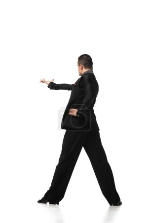 Photo pour Back view of stylish tango dancer inviting to dance on white background - image libre de droit