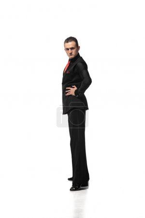 Photo pour Confident, elegant tango dancer looking at camera while standing with hand on hip on white background - image libre de droit
