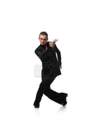 Photo pour Beau, danseur élégant regardant la caméra tout en effectuant tango sur fond blanc - image libre de droit