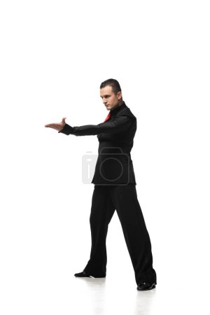 Photo pour Expressive tango dancer in elegant black suit inviting to dance on white background - image libre de droit