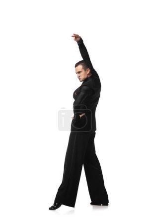 Photo pour Danseuse expressive en costume noir élégant exécutant tango avec la main sur la hanche sur fond blanc - image libre de droit