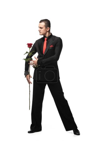 Photo pour Expressive dancer in elegant black suit performing tango with black rose on white background - image libre de droit