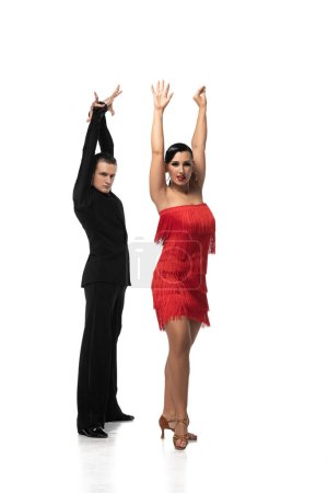 Photo pour Expressive couple of dancers looking at camera while performing tango with raised hands on white background - image libre de droit