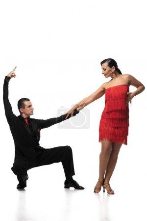 Photo pour Élégant danseur accroupi et tenant la main d'un partenaire attrayant tout en exécutant le tango sur fond blanc - image libre de droit