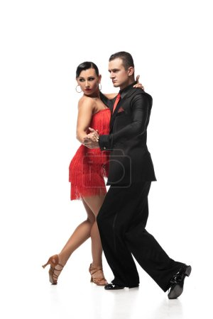 Photo pour Elegant, expressive couple of dancers performing tango on white background - image libre de droit