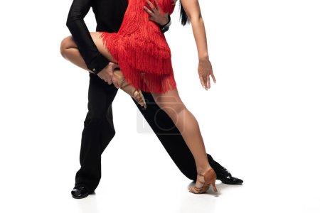 Photo pour Vue recadrée du danseur soutenant la jambe du partenaire tout en exécutant le tango sur fond blanc - image libre de droit