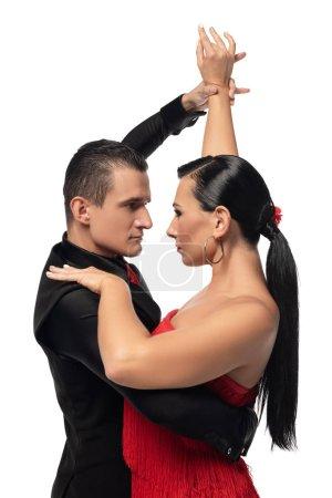 Photo pour Danseurs passionnés se regardant tout en exécutant tango isolé sur blanc - image libre de droit
