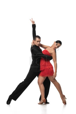 Photo pour Danseur élégant montrant geste de victoire tout en exécutant le tango avec un beau partenaire sur fond blanc - image libre de droit