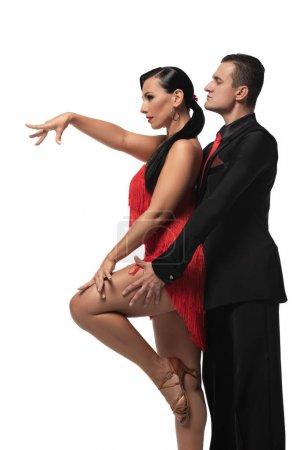 Photo pour Vue latérale de danseurs expressifs et élégants exécutant le tango isolé sur blanc - image libre de droit