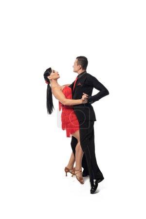 Photo pour Couple de danseurs élégants se regardant tout en exécutant le tango sur fond blanc - image libre de droit