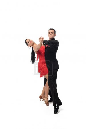 Photo pour Couple of elegant dancers looking at camera while performing tango on white background - image libre de droit