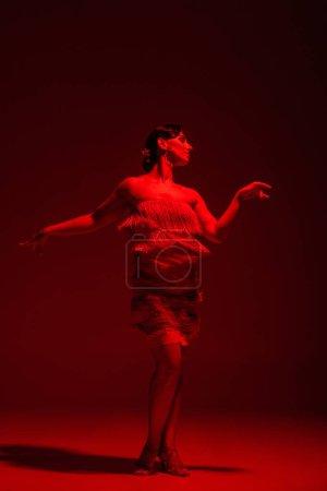 Photo pour Belle danseuse en robe avec frange exécutant tango sur fond sombre avec éclairage rouge - image libre de droit