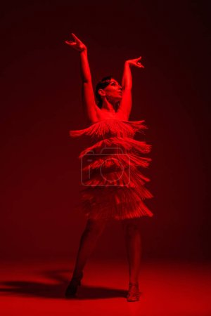 Photo for Beautiful dancer in dress with fringe dancing tango on dark background with red illumination - Royalty Free Image