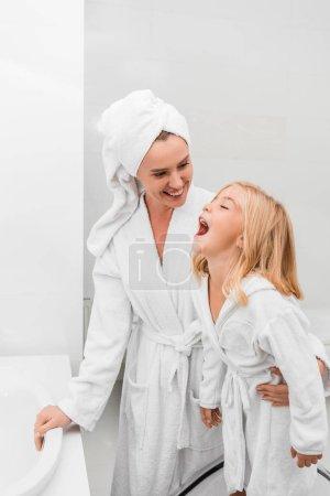 Photo pour Happy mother looking at cute daughter in bathroom - image libre de droit