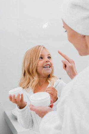 Photo pour Mère appliquant de la crème cosmétique sur le visage propre de sa fille heureuse - image libre de droit