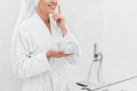 cropped view of smiling woman applying cosmetic cream on clean face