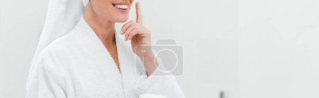 Photo pour Prise de vue panoramique de la femme appliquant la crème cosmétique sur le visage propre - image libre de droit