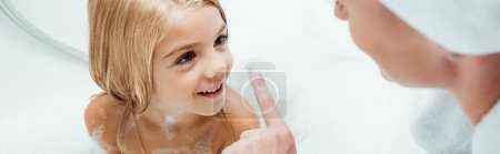 Photo pour Panoramic shot of adorable kid looking at mother in bathroom - image libre de droit