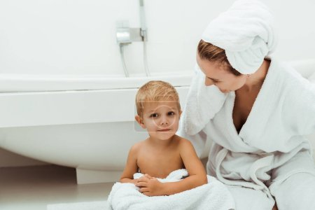 Photo for Happy mother smiling while looking at toddler boy in bathroom - Royalty Free Image