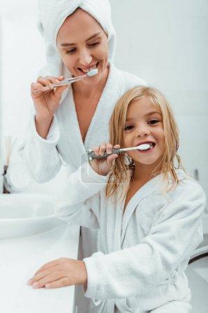 Photo pour Enfant heureux brossant les dents près de belle mère en peignoir - image libre de droit
