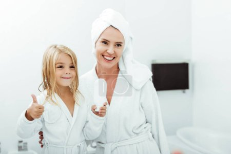 Photo for Cheerful kid holding white bottle and showing thumb up near mother in towel and bathrobe - Royalty Free Image