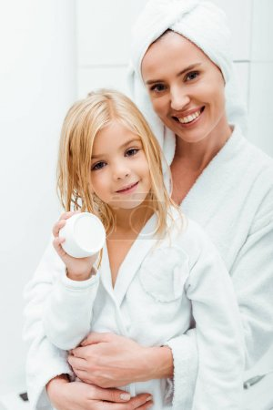 Photo for Happy mother hugging cute kid holding container with cosmetic cream - Royalty Free Image