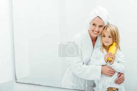 Photo for Cheerful mother hugging daughter with bottle of shampoo - Royalty Free Image