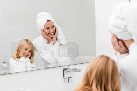 Photo pour Selective focus of cheerful mother and cute daughter in bathrobes touching faces in bathroom - image libre de droit