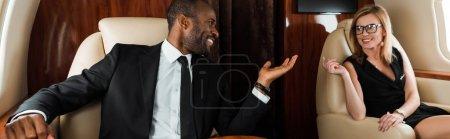 Photo pour Plan panoramique de heureux homme d'affaires afro-américain gesticulant près d'une femme d'affaires en jet privé - image libre de droit