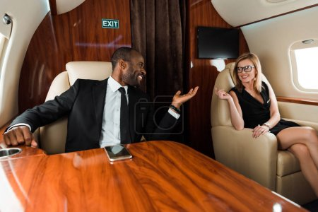 happy african american businessman gesturing near businesswoman in private jet