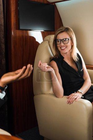 Foto de Enfoque selectivo de la mujer de negocios gesto cerca de hombre afroamericano en jet privado - Imagen libre de derechos