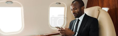 panoramic shot of handsome african american businessman using smartphone in private jet