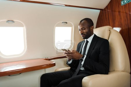Photo pour Handsome african american businessman using smartphone in private jet - image libre de droit