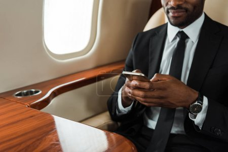 Photo pour Cropped view of african american businessman in suit using smartphone in private jet - image libre de droit