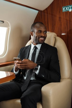 Photo for Cheerful african american businessman in suit using smartphone in private jet - Royalty Free Image