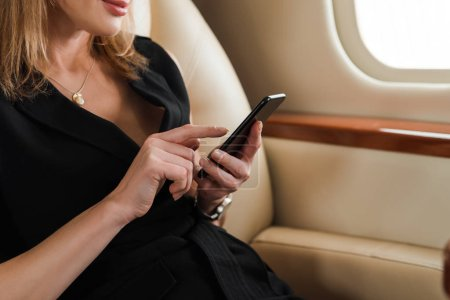 Photo pour Cropped view of businesswoman using smartphone in private jet - image libre de droit