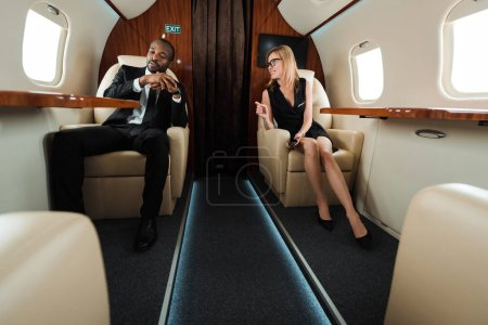 Photo pour Selective focus of happy businesswoman and african american businessman in private jet - image libre de droit