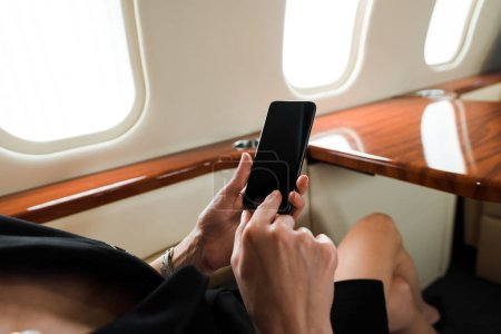 Photo pour Cropped view of businesswoman holding smartphone with blank screen in private jet - image libre de droit