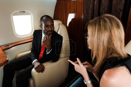 Photo for Selective focus of happy african american businessman looking at businesswoman in private plane - Royalty Free Image