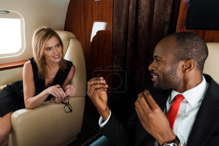 handsome african american man gesturing while looking at woman in private jet