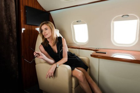 Photo pour Attractive businesswoman in dress holding glasses while sitting  in private jet - image libre de droit