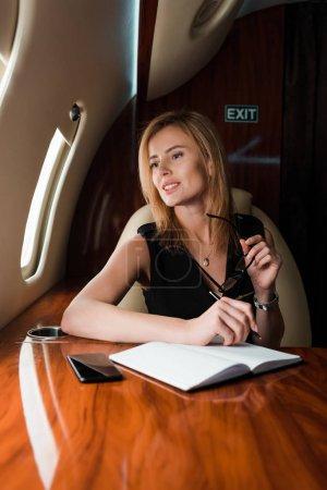 Selektiver Fokus der fröhlichen Geschäftsfrau mit Stift und Brille in der Nähe von Notebook und Smartphone mit leerem Bildschirm