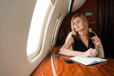 Photo for Selective focus of pensive businesswoman holding pen and glasses near notebook and smartphone with blank screen - Royalty Free Image