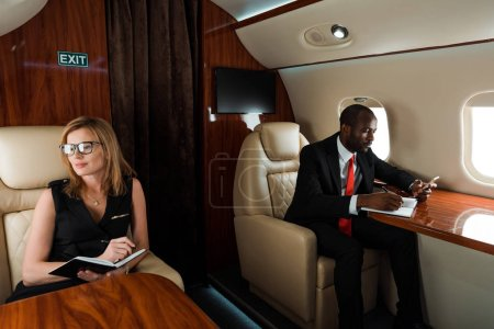 Photo for African american businessman using smartphone near businesswoman writing in notebook in private jet - Royalty Free Image