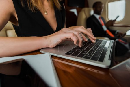 Photo for Selective focus of businesswoman typing on laptop near african american businessman in plane - Royalty Free Image