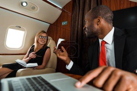 selektiver Fokus einer Geschäftsfrau, die in der Nähe eines afrikanisch-amerikanischen Geschäftsmannes mit Laptop gestikuliert